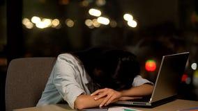 Tr?ttad ung dam som sover p? tabellen, k?nsla som i regeringsst?llning borras, arbetsutmattning arkivfoto