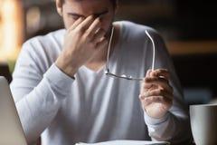 Tröttat av datoraffärsman känner att ta av exponeringsglas eyestrain arkivfoton
