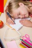Tröttat av skolflicka sovande på skrivbordet Royaltyfria Foton