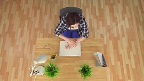 Tröttat och evakuerat av arbetet av en ung kvinna på en bärbar dator arkivfilmer