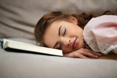 Tröttat ta för kvinna ta sig en tupplur hemma ligga på en soffa med en bok royaltyfri fotografi