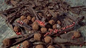 Trüffeln in der dunklen Schokolade mit rotem Pfeffer und Schokoladensplittern stock video footage