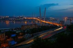 Tr?fico de coche cable-permanecido de oro del camino del puente desde arriba Iluminaci?n moderna de la noche de Vladivostok Rusia imagenes de archivo