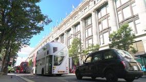 Tr?fico de espera de movimiento lento, taxis y autobuses rojos de Londres del autob?s de dos pisos conduciendo m?s all? de Selfri metrajes