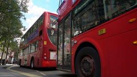 Tr?fico de espera de movimiento lento, taxis y autobuses rojos de Londres del autob?s de dos pisos conduciendo m?s all? de Selfri almacen de metraje de vídeo
