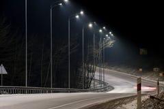 Tr?fico r?pido en la noche Estaci?n del invierno concepto del camino, el retiro de nieve y de hielo, el peligro y la seguridad de foto de archivo