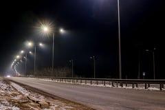 Tr?fico r?pido en la noche Timelapse Estaci?n del invierno concepto del camino, el retiro de nieve y de hielo, el peligro y la se foto de archivo