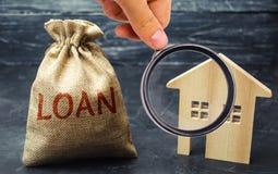 Tr?hus och en p?se med ordl?net K?pa ett skuldsatt hem Familjinvestering i fastighet- och riskledningbegrepp royaltyfri fotografi