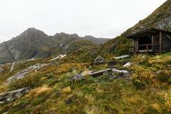 Tr?kabin i bergen p? Lofoten ?ar i Norge p? kusten royaltyfri foto