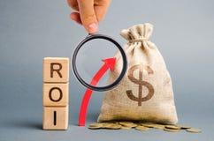 Tr?kvarter med ordet ROI och den ?vre pilen med pengarp?sen P? h?g niv? av aff?rsvinst Retur p? investering, royaltyfria bilder