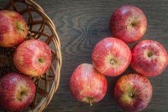 Tr?m?rk bakgrund Röda äpplen på träbakgrund, i en korg Lekmanna- l?genhet, b?sta sikt, utrymme f?r text royaltyfri foto