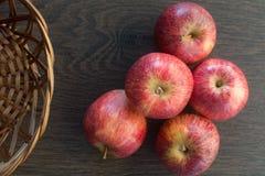 Tr?m?rk bakgrund Röda äpplen på träbakgrund, i en korg som skapar en gammal och lantlig atmosfär Framst?llning av arkivfoto
