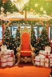 Trône rouge d'or de bureau du ` s de Santa avec les cadeaux blancs avec le ruban rouge Photographie stock
