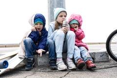 Tr?s crian?as patinaram em um skate e em uma bicicleta e sentaram-se para baixo para descansar no freio fotografia de stock royalty free