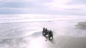 Tr?s homens consider?veis do moderno que montam o piloto feito sob encomenda moderno do caf? da motocicleta na praia preta da are filme