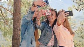 Tr?s jovens mulheres que tomam o selfie com telefone celular vídeos de arquivo