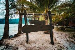 Tr?signboard p? tropisk strand Ett teckenbräde för namnet av hotellet eller stranden på en bakgrund av den härliga naturen på arkivbild