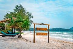 Tr?signboard p? tropisk strand Ett teckenbr?de f?r namnet av hotellet eller stranden p? en bakgrund av den h?rliga naturen p? royaltyfria bilder