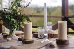 Tr?tabellupps?ttning med stearinljus och blommor utomhus arkivfoton