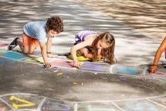 Tração de duas crianças fora em amarelinhas do giz fotografia de stock