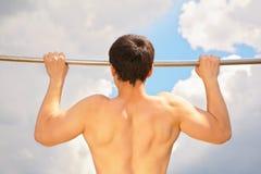 Tração do atleta oneself acima no fundo do céu Fotos de Stock Royalty Free