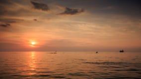 Trações do barco da nadada das silhuetas no mar na reflexão de Sun do por do sol