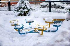 Trações e restos da neve no campo de jogos em uma das cidades de Rússia no inverno imagem de stock