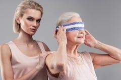 Traçage de la belle fille blonde bloquant la vision de la vieille femme impuissante photos stock