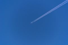 Traço diagonal do avião em um céu azul claro Foto de Stock Royalty Free