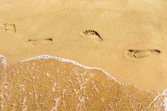Traços de pés e de água humanos na areia Foto de Stock Royalty Free