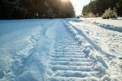 Traços de um carro de neve no sol da neve Imagem de Stock Royalty Free