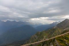 Traînée de suspension au-dessus d'un précipice et un arc-en-ciel dans les montagnes de Caucase sous un ciel orageux, région de Kr photographie stock