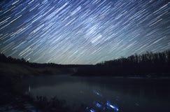 Traînées d'étoile à la nuit et à la rivière Photos stock