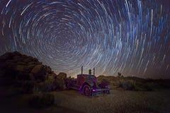 Traînées d'étoile au-dessus d'un camion abandonné Photo stock