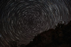 Traînées d'étoile la nuit au-dessus des roches Photographie stock libre de droits