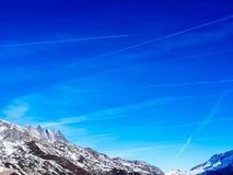 Traînées d'avion au-dessus des Alpes Image libre de droits