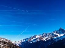 Traînées d'avion au-dessus des Alpes Images libres de droits