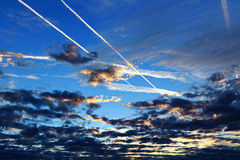 Traînées d'avion au-dessus des nuages par heure bleue Photographie stock libre de droits