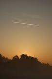 Traînées d'avion au lever de soleil Photos libres de droits