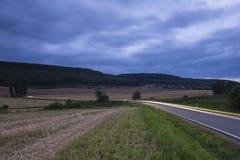 Traînées de lumière par les collines Photos stock