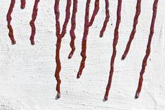 Traînées de peinture rouge sur le mur blanchi Photographie stock