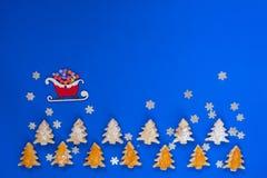 Traîneau du ` s de Santa, avec des cadeaux, volant au-dessus des biscuits Image libre de droits