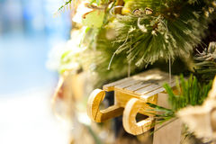 Traîneau en bois de jouet de Noël vieux accrochant sur les bougies brûlantes de branche, boîtes, boules, cônes de pin, noix, Bran Photographie stock libre de droits