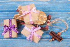 Traîneau en bois et cadeaux enveloppés avec des rubans pour Noël ou toute autre célébration sur les conseils bleus Photographie stock