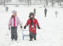 Traîneau heureux de neige de deux enfants photos stock