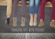 Traîner avec le groupe de personnes d'amis les jambes se reposant sur le bois Photos stock