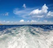 Traînez à gauche en le bateau dans l'eau avec le voilier blanc images libres de droits