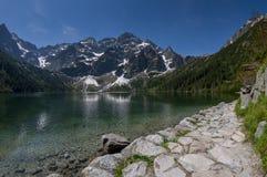 Traînez au lac de montagne avec les sommets rocheux reflétés dans l'eau photo libre de droits