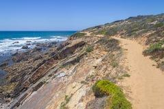 Traînez dans les falaises sur la plage, Vila Nova de Milfontes image libre de droits