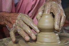 Traînez en créant le pot sur la roue de poterie utilisant l'argile images stock